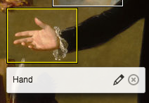 "The same image of a hand with palm upturned as before. This time the highlight of the rectangle surrounding the hand is yellow, not white, and the area below it has a caption ""hand"" to the left of a pencil icon for edit and an x in a circle icon for delete"